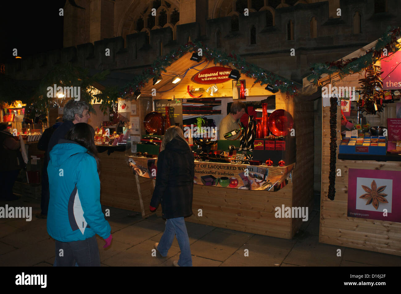a stall selling christmas gifts with bath abbey in the distance at the bath christmas market