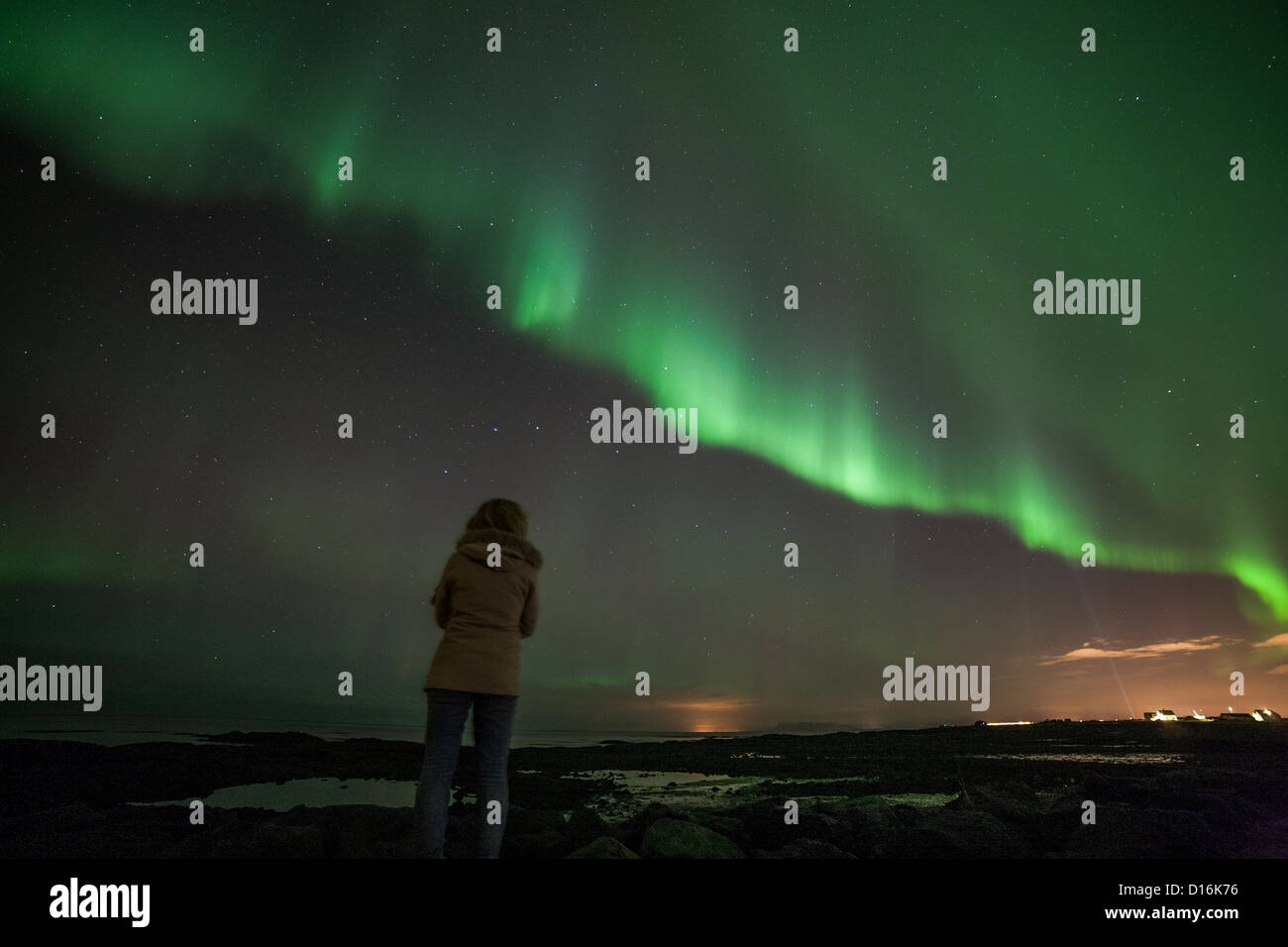 woman with her back to us, wearing jacket and jeans, watching the aurora borealis in iceland - Stock Image