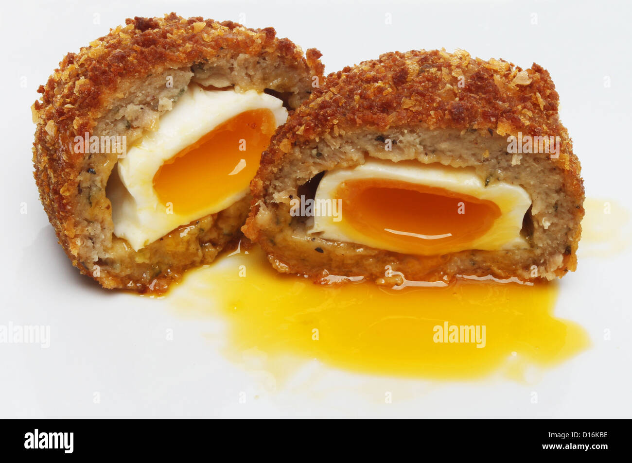 Closeup of a runny yolk Scotch egg on a plate - Stock Image
