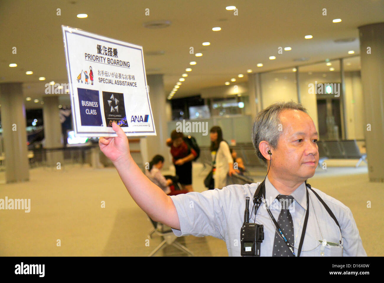 Tokyo Japan Narita International Airport NRT gate area concourse ANA Al Nippon Airways Asian man uniform holding - Stock Image