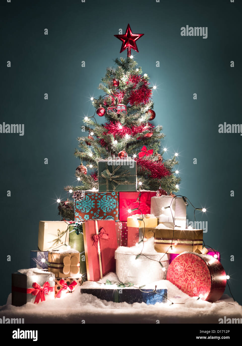 green christmas tree with beatiful red decorations surrounded by a heap of gift boxes covered with - Green Christmas Tree With Blue Decorations