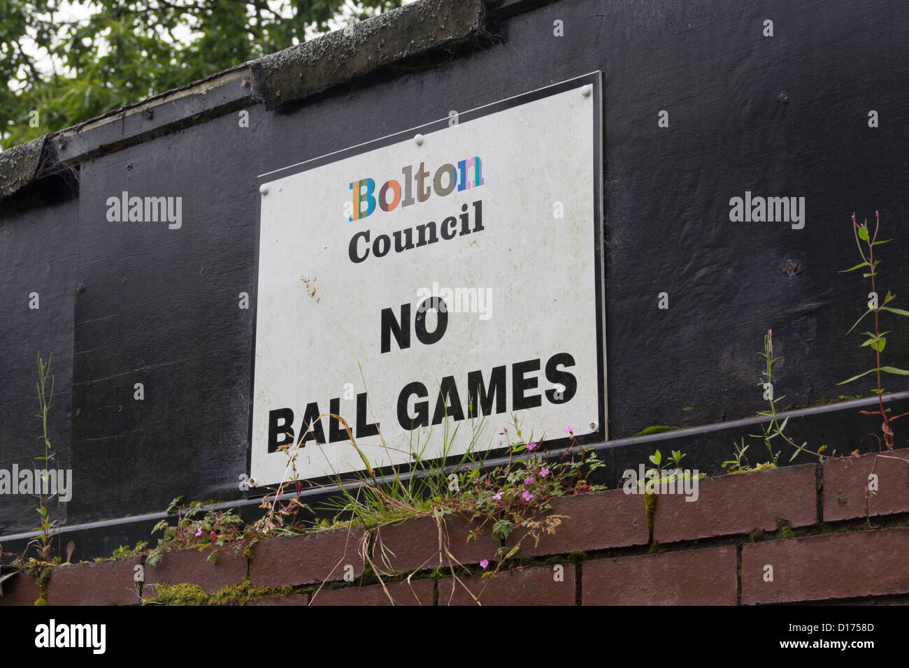 No Ball Games sign placed by Bolton Council, adjacent to a car parking area in Moss Bank Park. - Stock Image