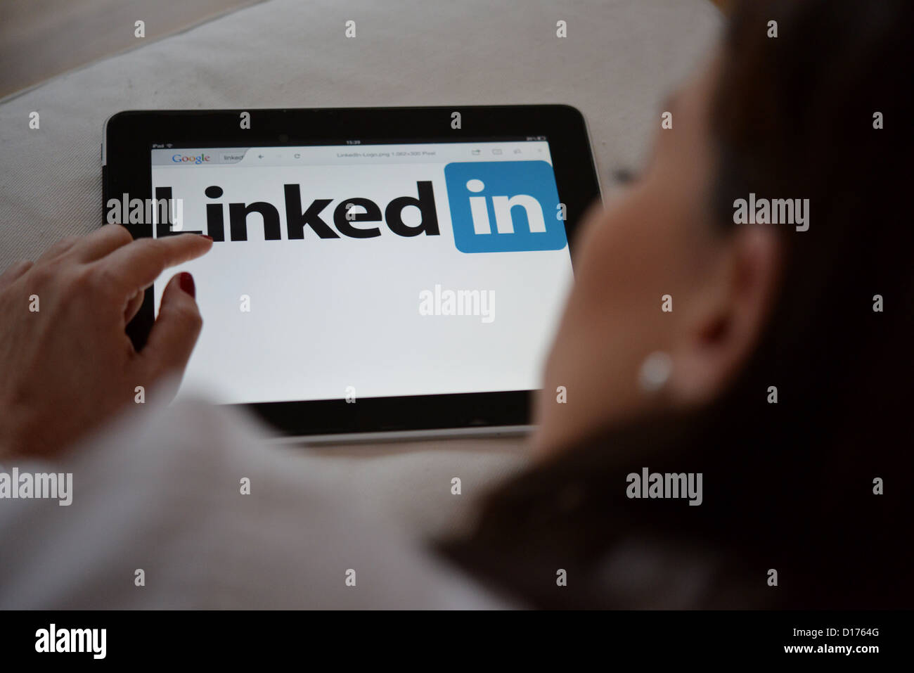 A businesswoman looking at the logo of linked in on a tablet computer. - Stock Image