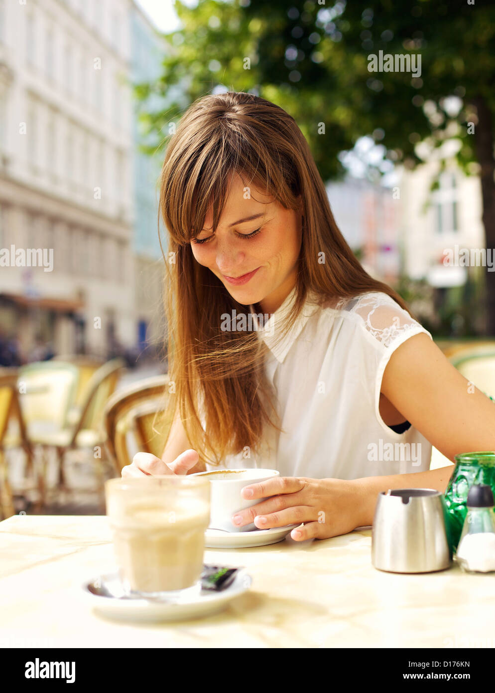 Smiling woman enjoying her espresso in an outdoor coffee shop - Stock Image