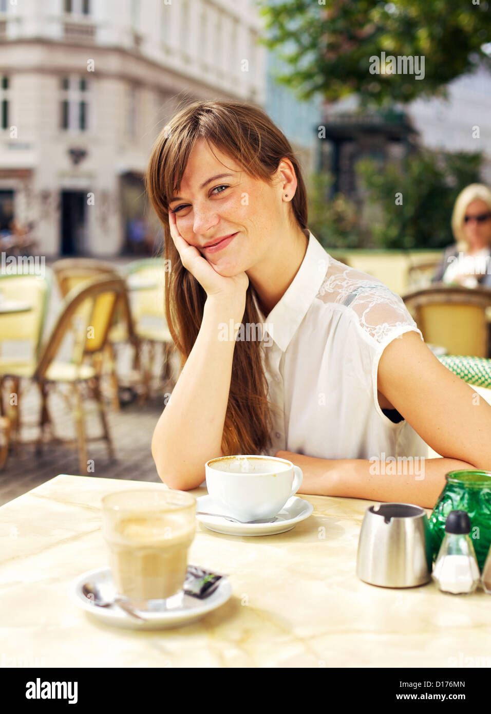 Beautiful relaxed woman smiling and enjoying the open air restaurant in the city - Stock Image