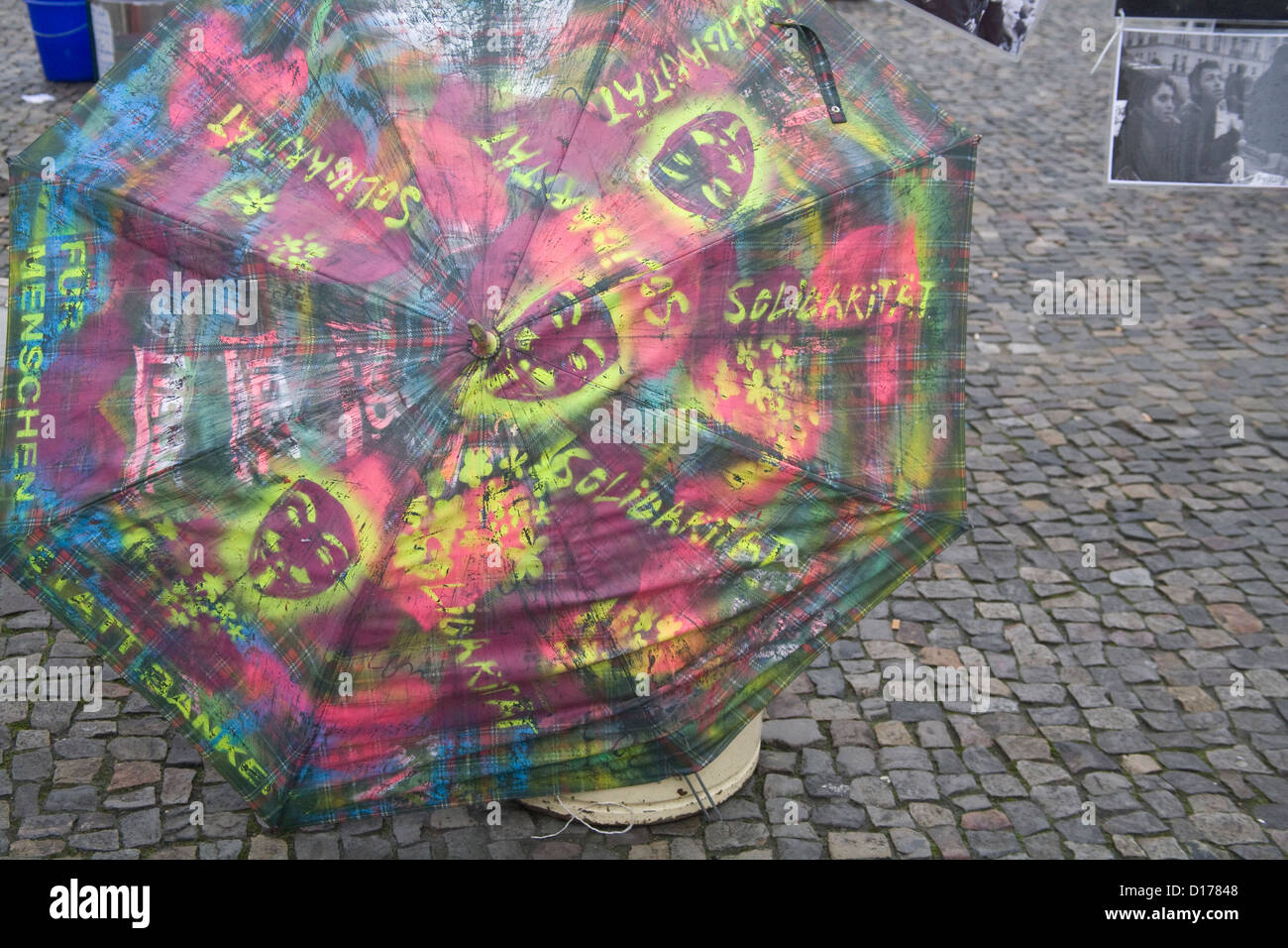 Berlin Germany EU Colourful umbrella with slogans painted as protest at deportation of Iranian asylum seekers - Stock Image