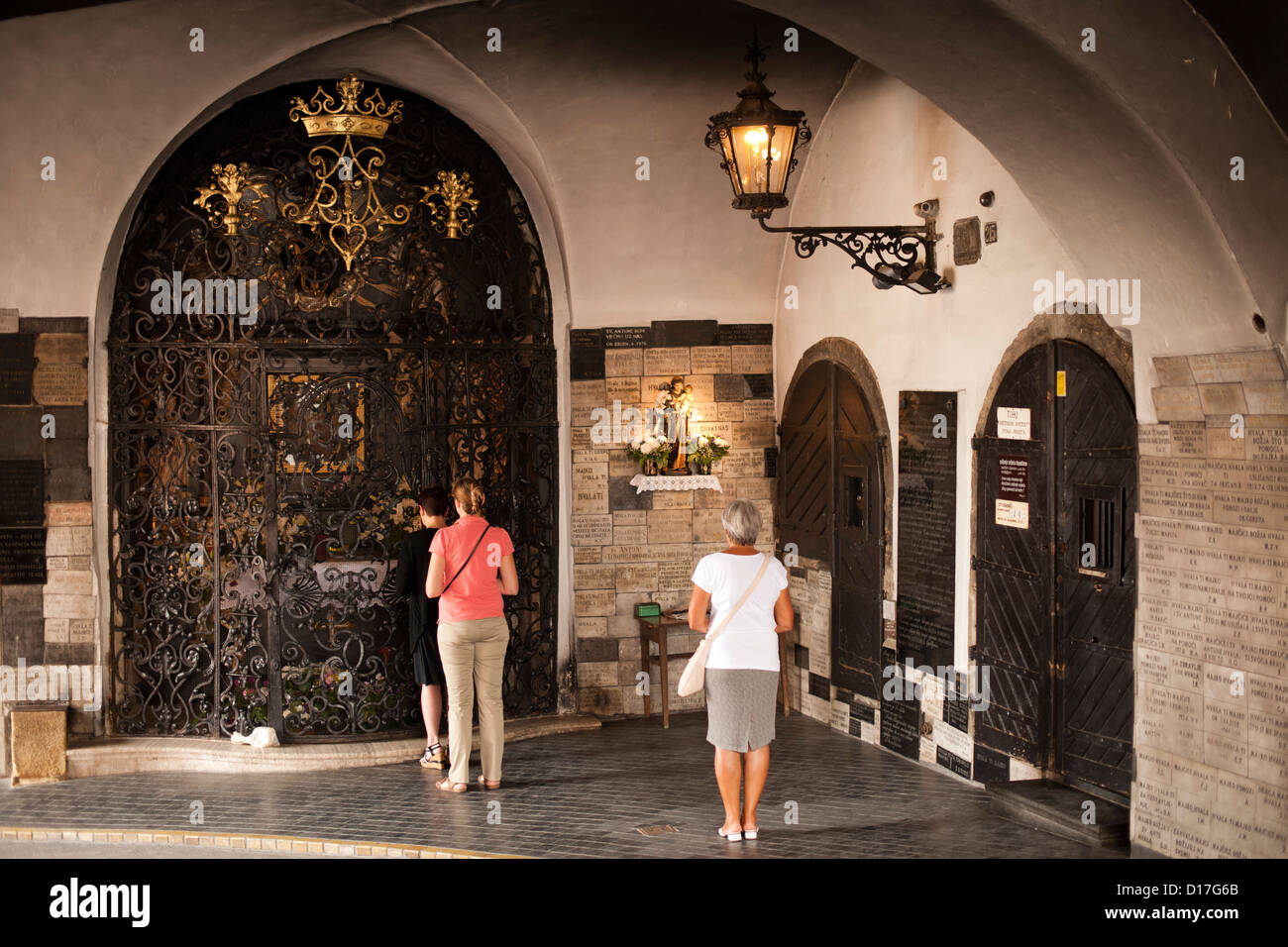 People praying at the Shrine to the Virgin Mary in the Stone Gate entrance to the old town in Zagreb, the capital - Stock Image