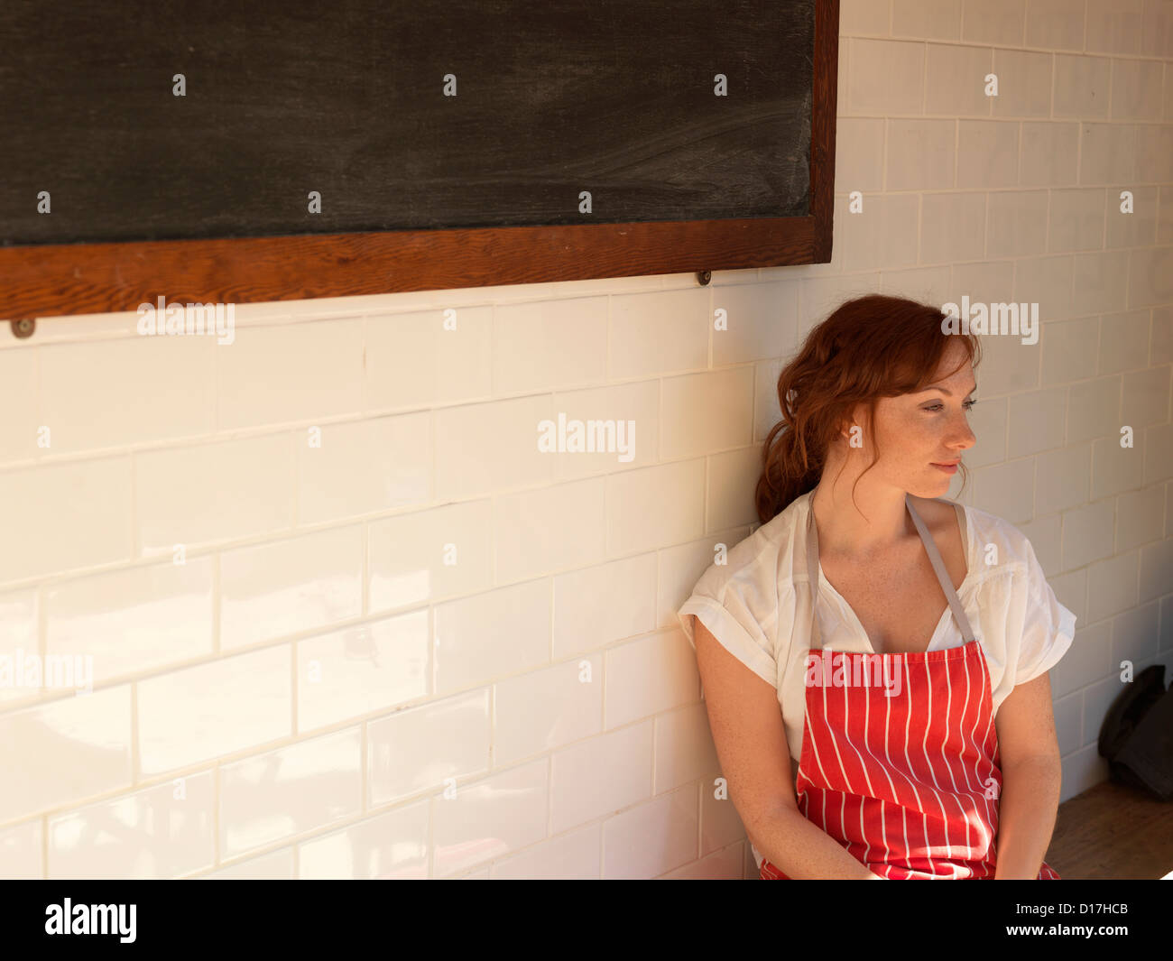 Woman in apron sitting on bench - Stock Image