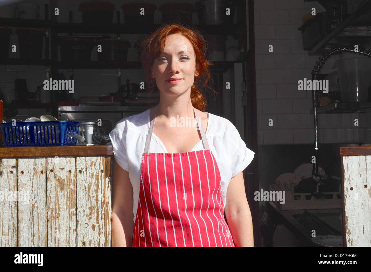 Woman in apron working outdoors - Stock Image