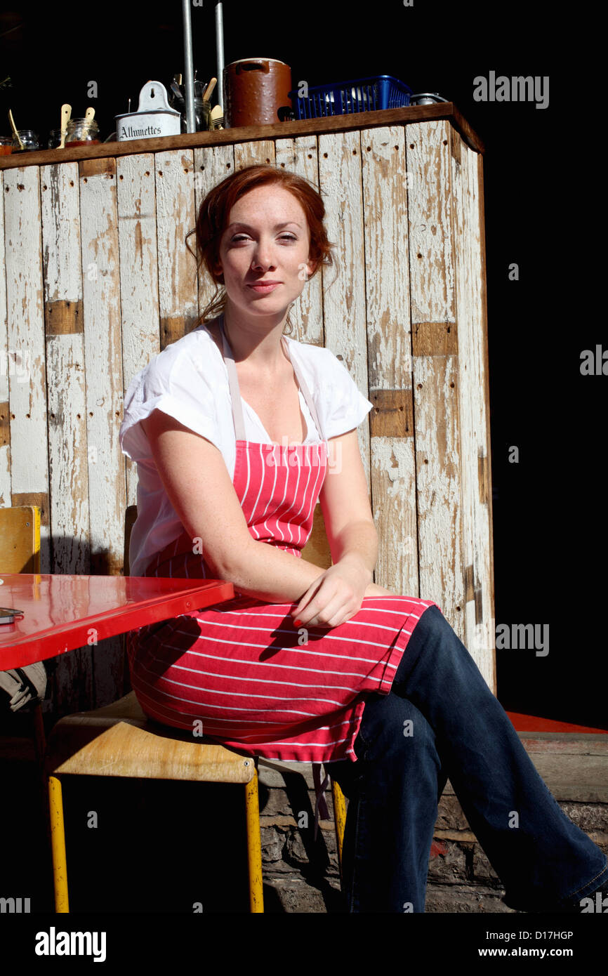 Woman in apron sitting outdoors - Stock Image