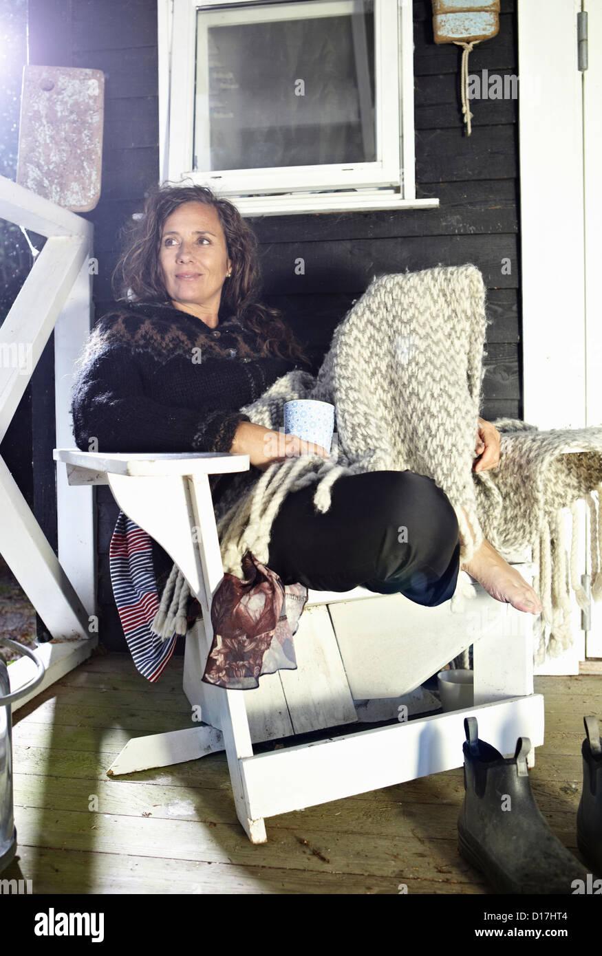 Woman relaxing in armchair indoors - Stock Image