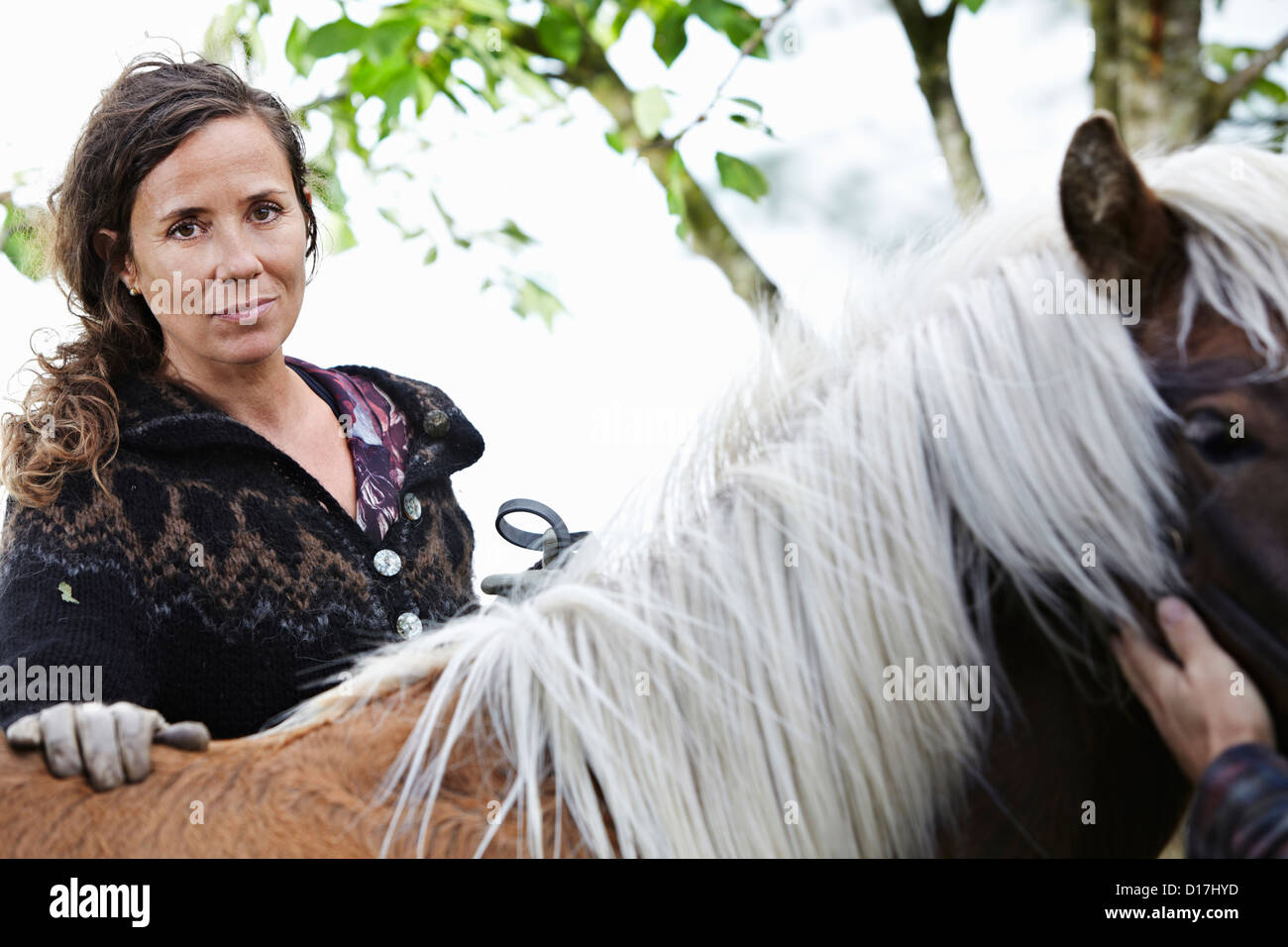 Woman petting horse outdoors - Stock Image