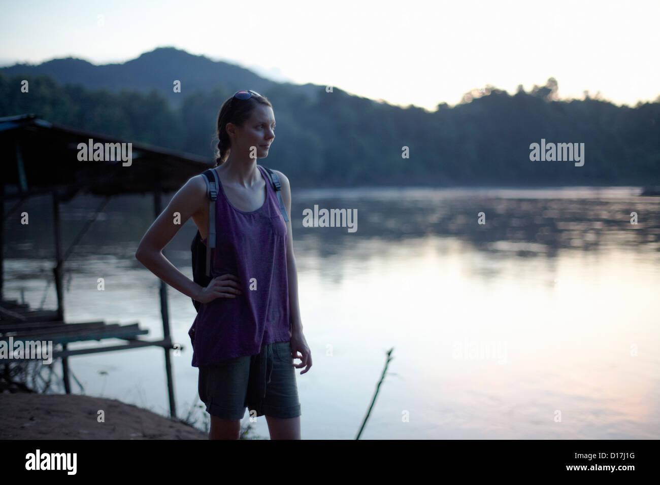 Woman walking by still lake - Stock Image