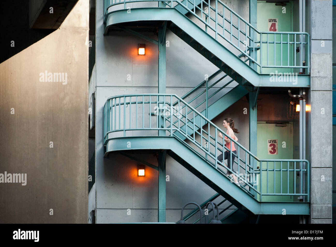 Woman running on apartment steps - Stock Image