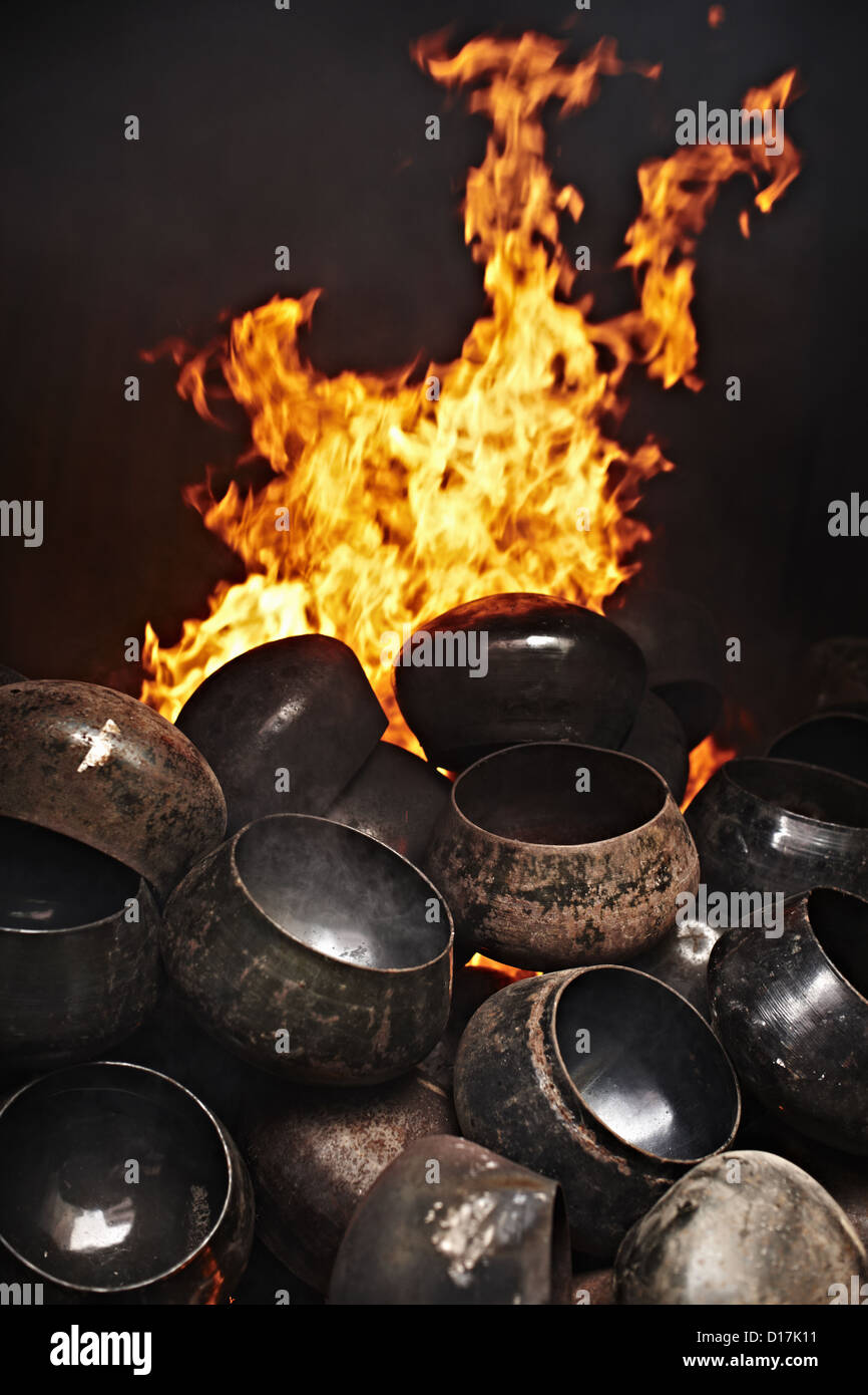 Metal pots piled by fire - Stock Image