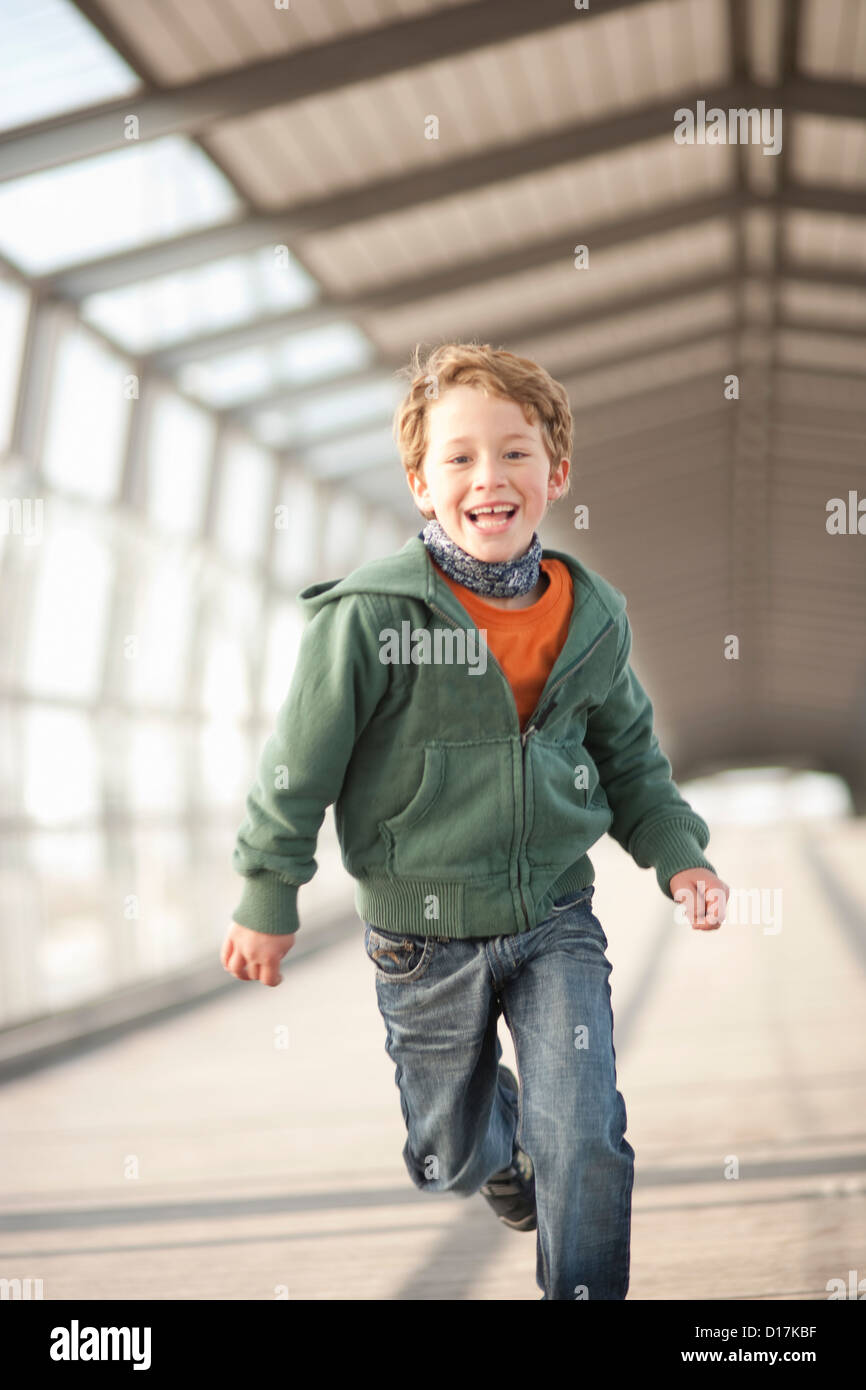 Smiling boy running in city tunnel Stock Photo