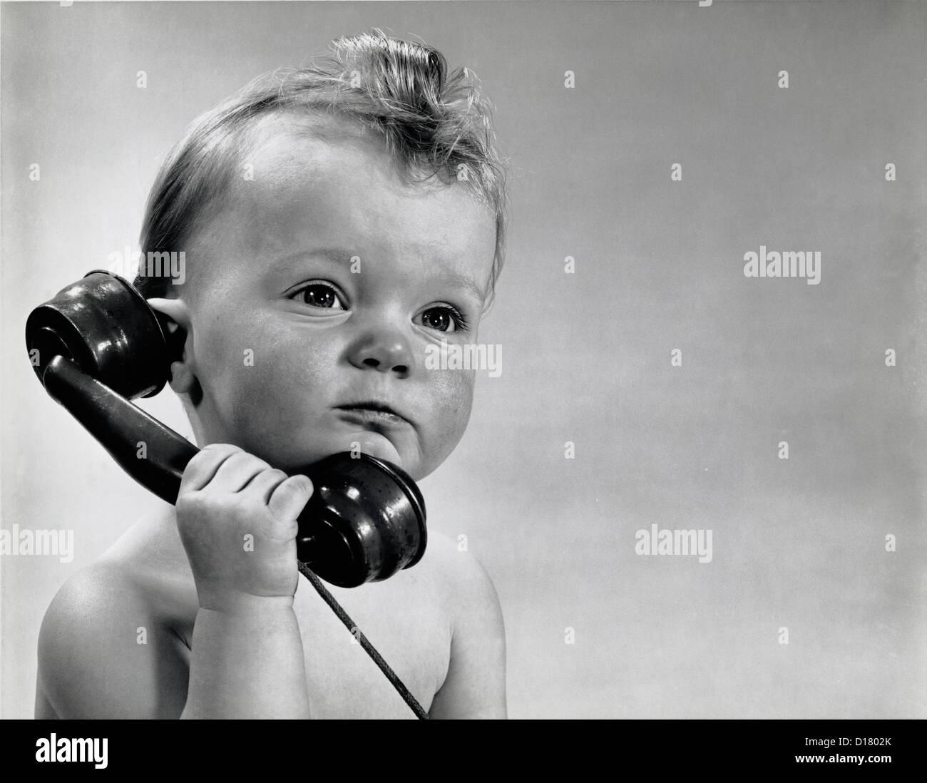 Vintage photo of baby boy talking on phone - Stock Image