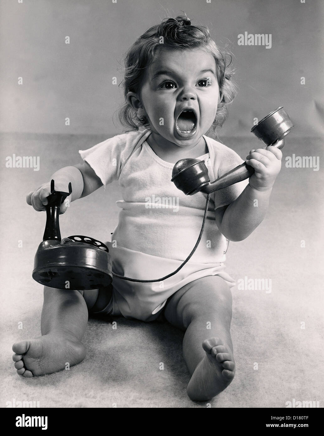 Vintage photo of infant screaming with phone - Stock Image