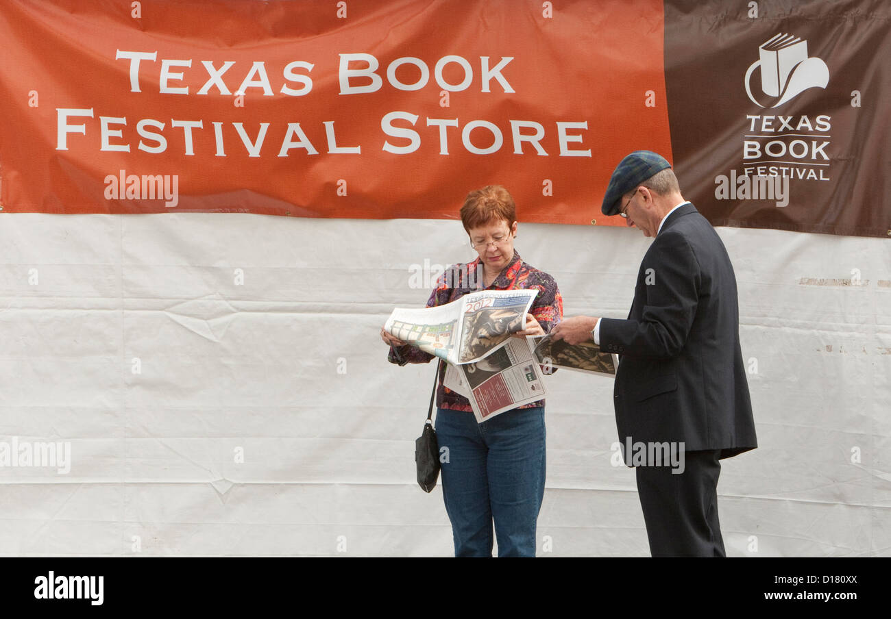 Middle age couple reviews and reads the paper schedule of the Texas Book Festival in Austin, Texas - Stock Image