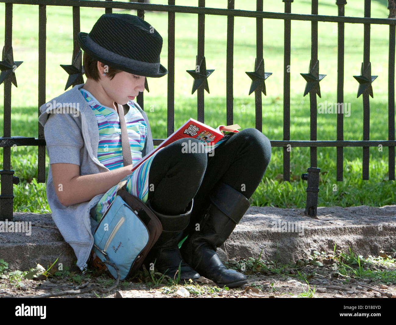 Young teenage girl wearing a black hat sits against fence as she reads book while attending the outdoor Texas Book - Stock Image