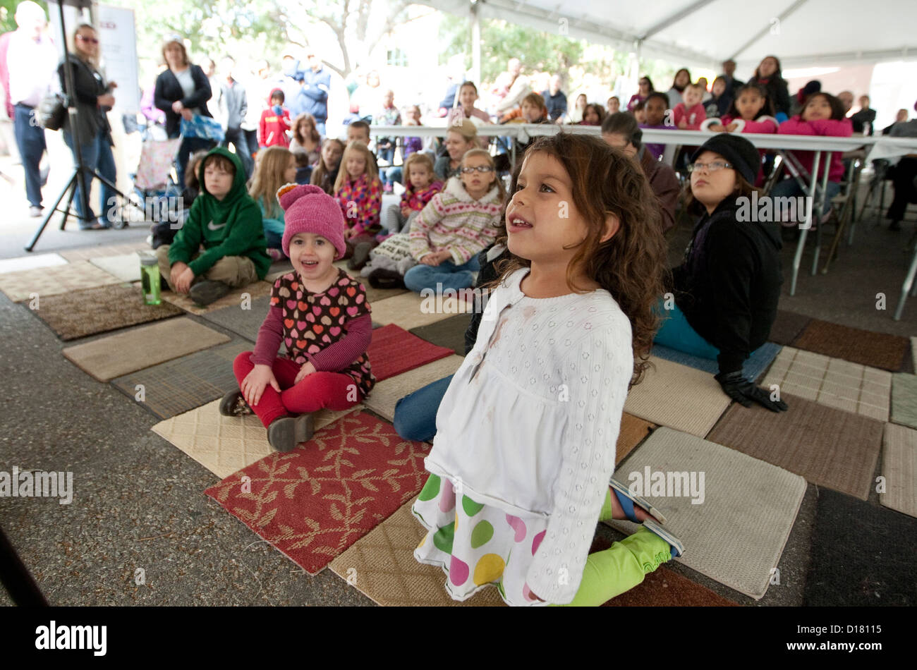 Smiling and happy children sit on carpet mats while listening to children's book author during the Texas Book - Stock Image