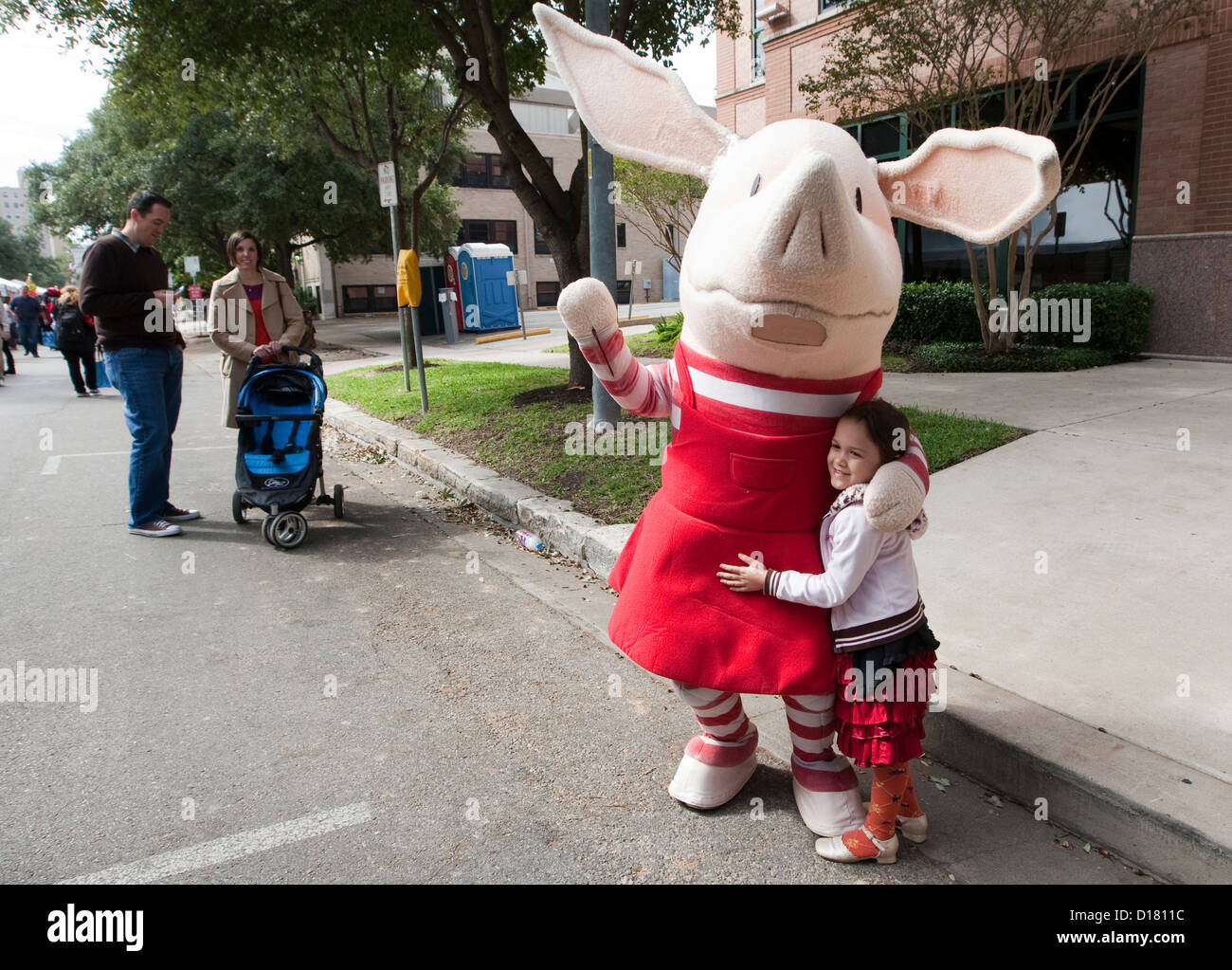 Young girl hugs children's book character Olivia during the Texas Book Festival in Austin, Texas - Stock Image