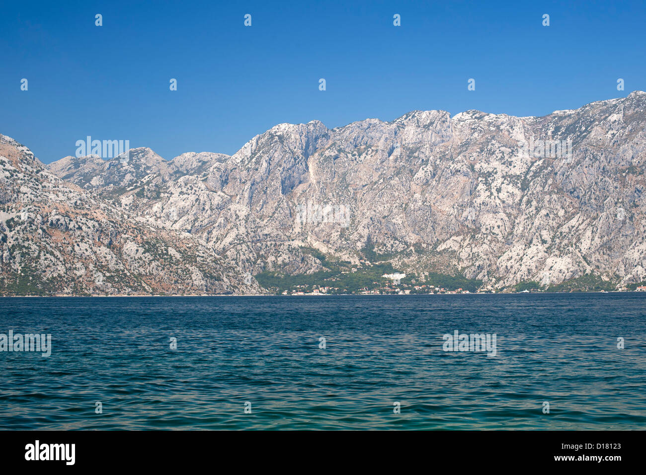 View of the mountains and houses lining the edge of Kotor Bay in Montenegro. - Stock Image