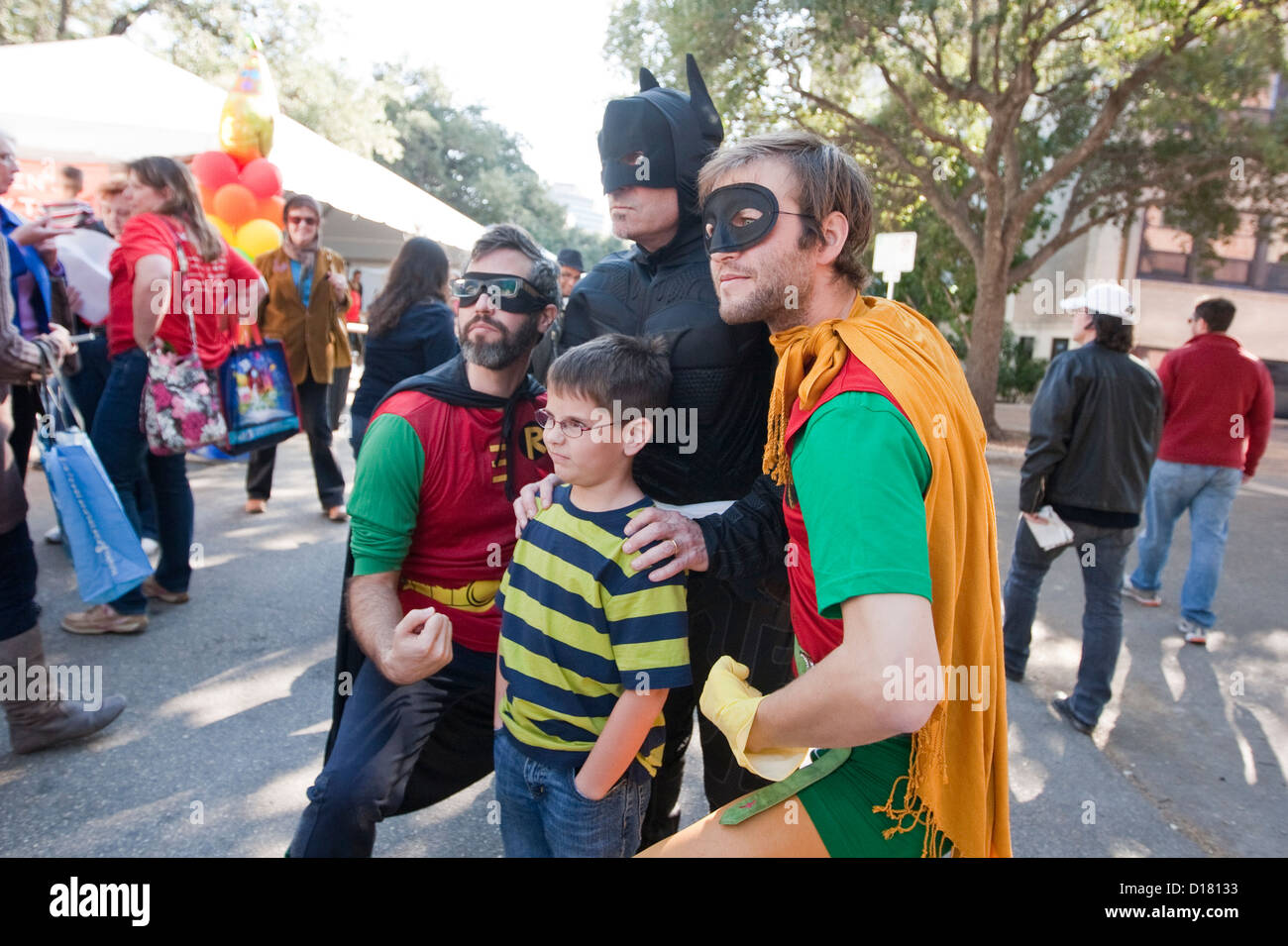 Young boy poses with several children's book authors dressed up in super hero costumes including Batman, Robin - Stock Image