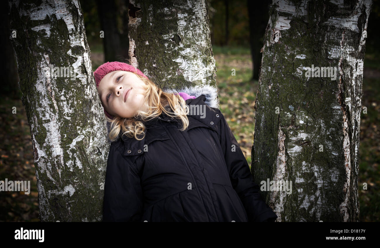 Little beautiful blond girl dreamily leaning on the birch - Stock Image