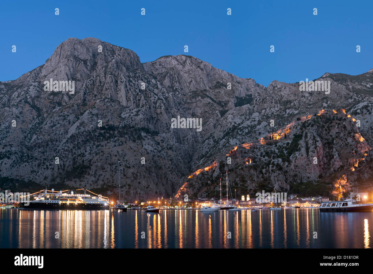 Dusk view of Kotor Bay, Kotor town and the fortifications overlooking the town in Montenegro. - Stock Image