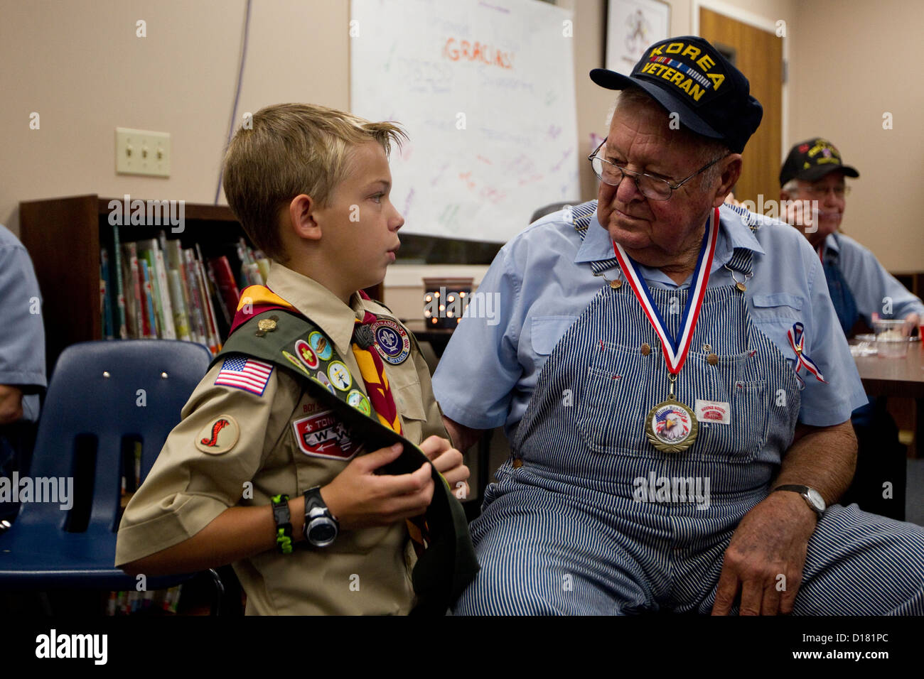 13 year old boy scout, shows elderly white male veteran, his merit badges during a Veteran's Day celebration - Stock Image