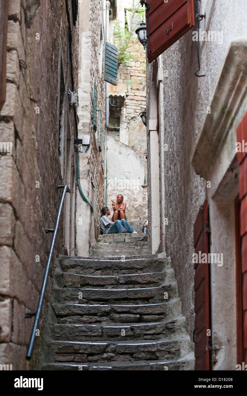 People sitting on a stone staircase in the old town of Kotor in Montenegro. - Stock Image