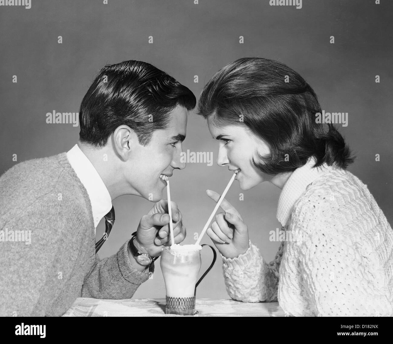 Historic shot of couple sharing ice cream soda at malt shop - Stock Image