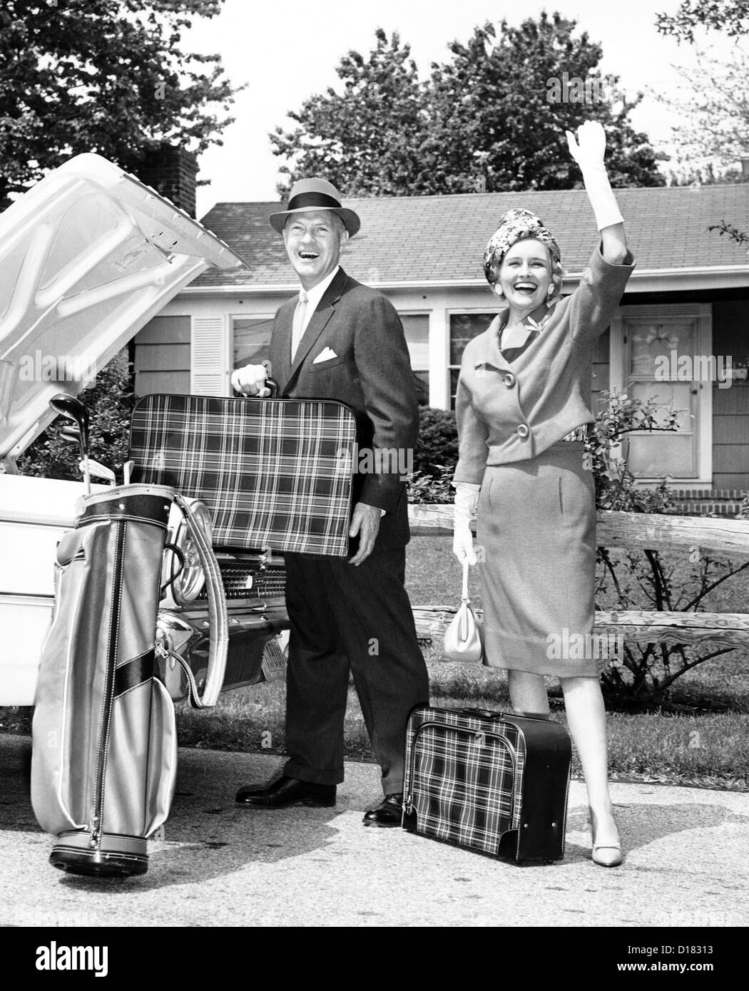 Mature couple loading car trunk for a trip - Stock Image