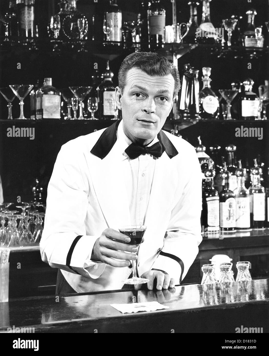 Portrait of a bartender holding a drink - Stock Image