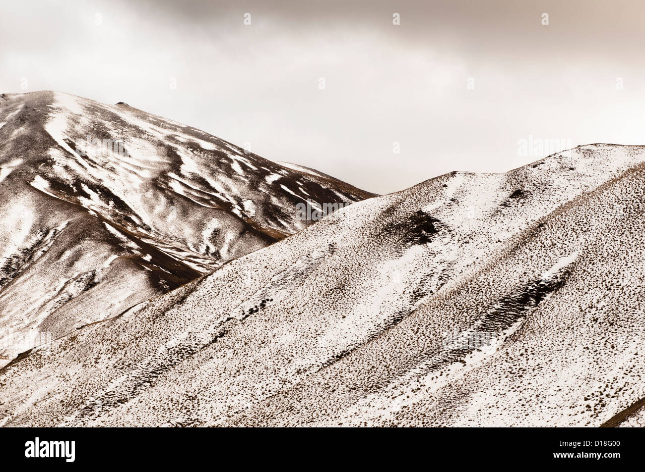 Grass and snow on mountainsides - Stock Image