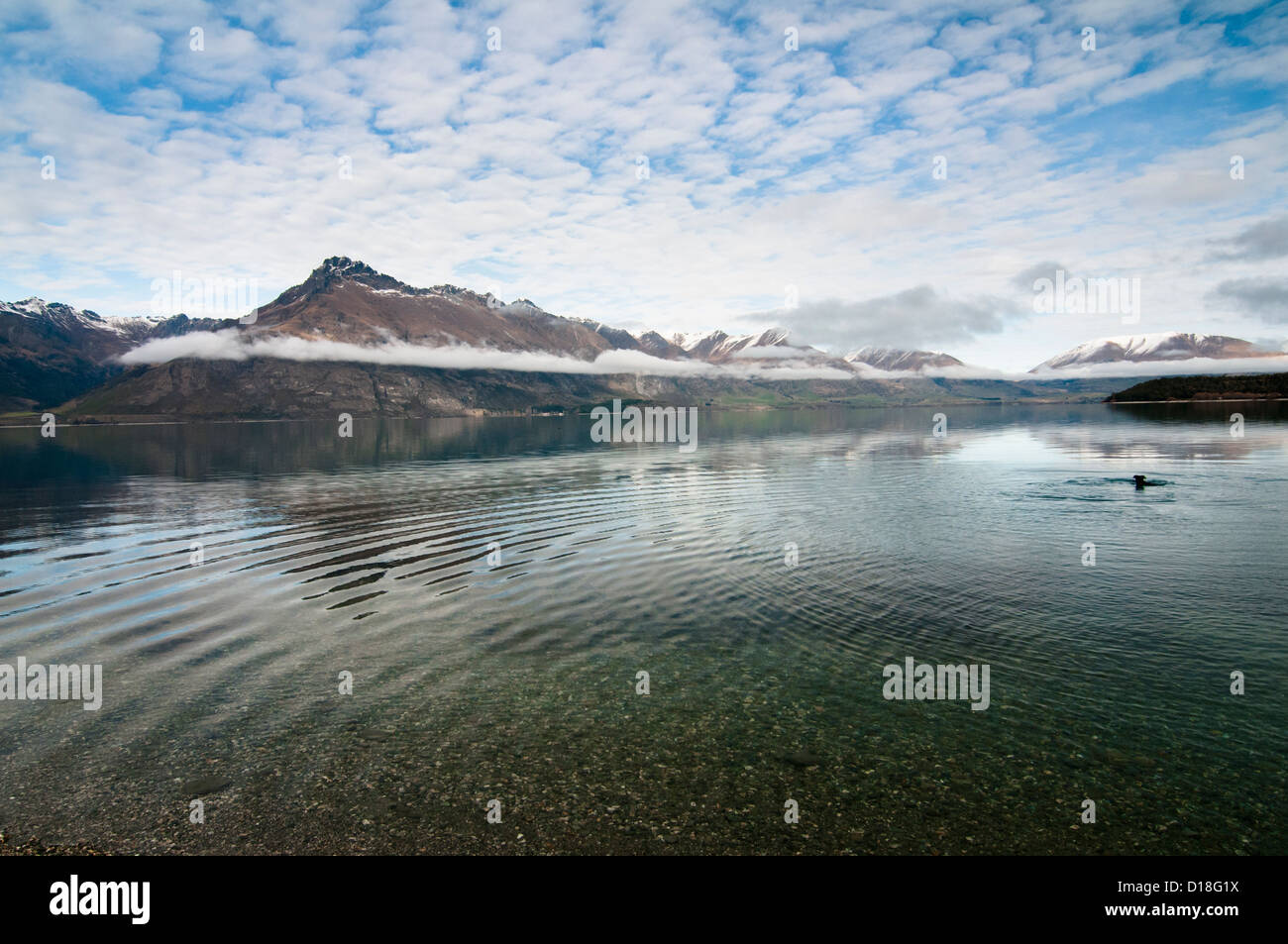 Clouds reflected in rippling lake - Stock Image