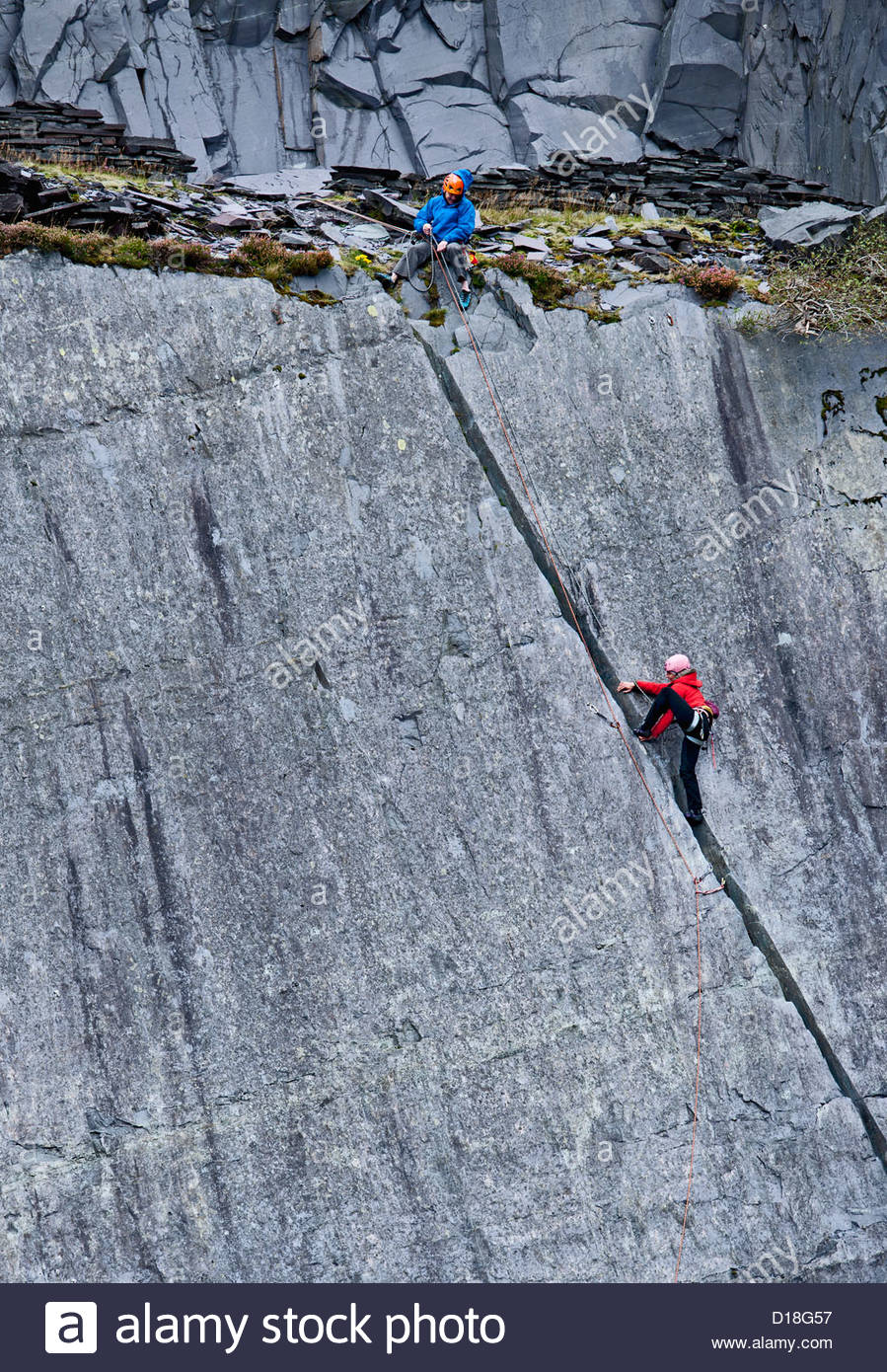 Climbers scaling steep rock face - Stock Image