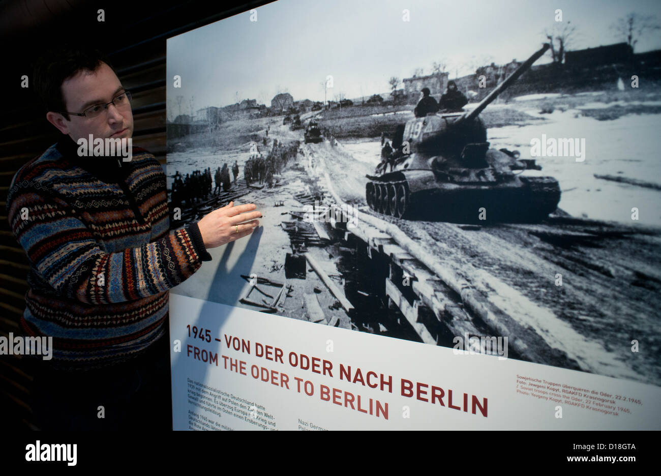 Curator of the new permanent exhibition, Sebastian Nagel, is pictured next to a historical photograph in Seelow - Stock Image
