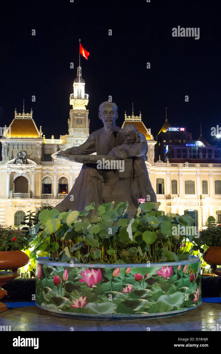 Statue of Ho Chi Minh cradling a child in front of City Hall (People's Committee Building) in Vietnam. - Stock Image