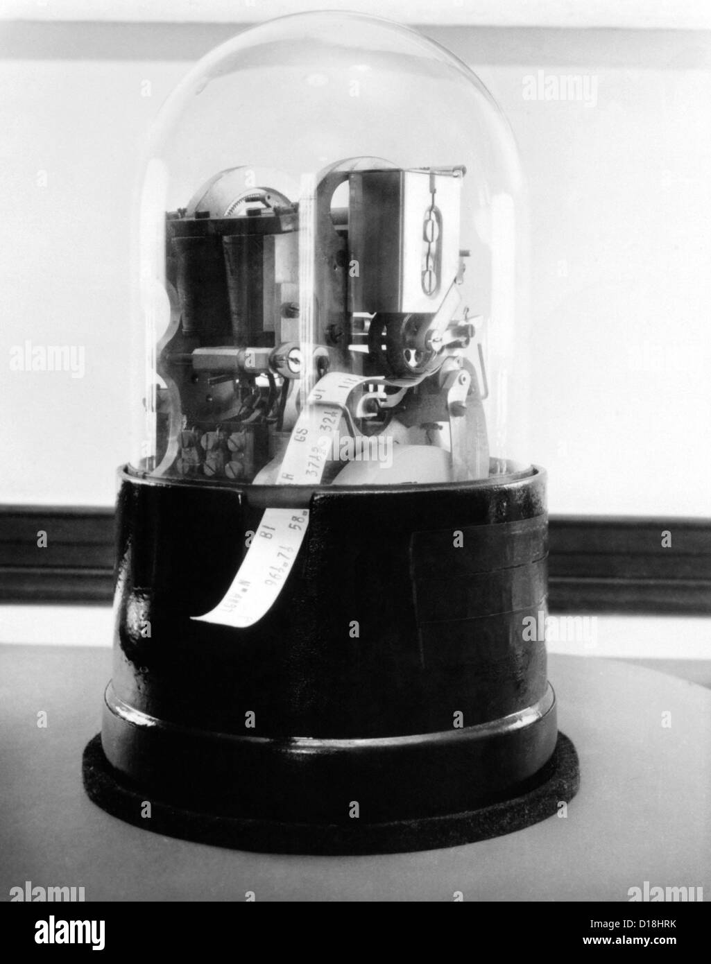 Classic 1920's stock ticker with a glass dome. Stock tickers were specialized telegraphs that conveying stock prices. Stock Photo