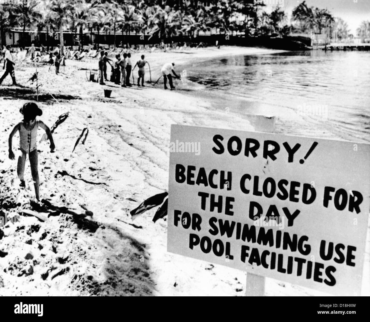 Puerto Rican Hilton Hotel beach closed by an oil spill. Workers in the background spray chemicals to clear the beach Stock Photo