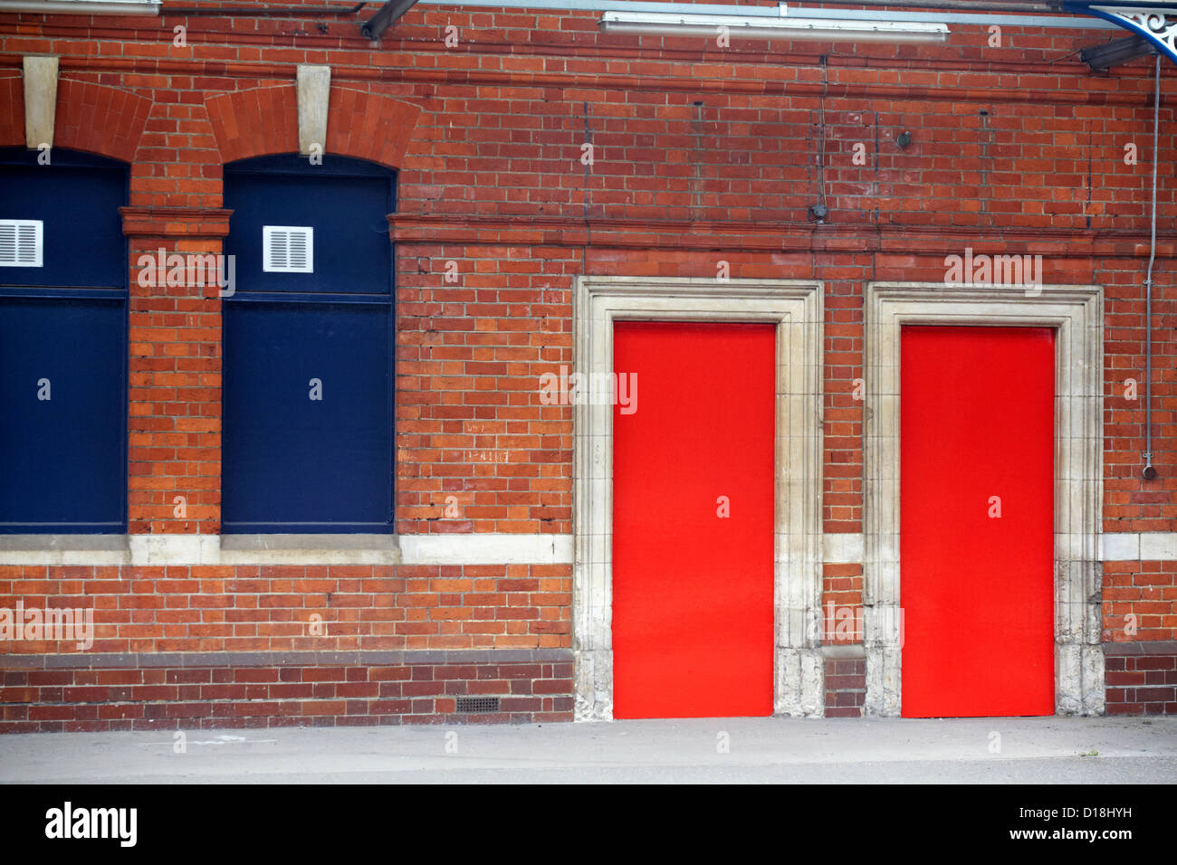 Two red doors on platform of railway station - Stock Image