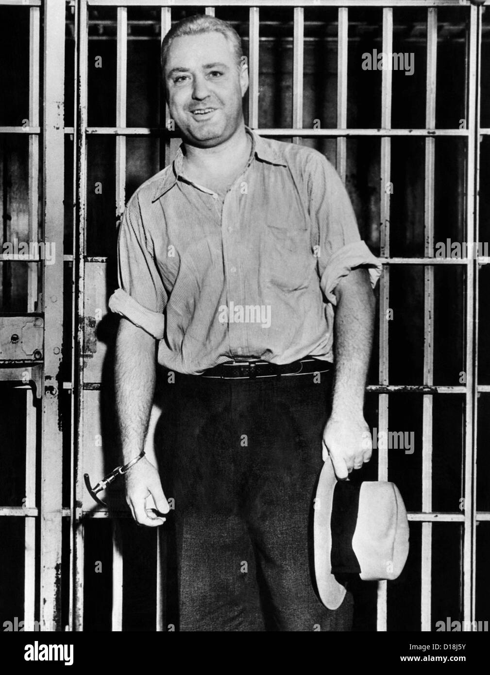 'Machine Gun' Kelly, handcuffed to cell bars, smiles for photographers in his Memphis jail cell. Sept. 26, 1933. Stock Photo