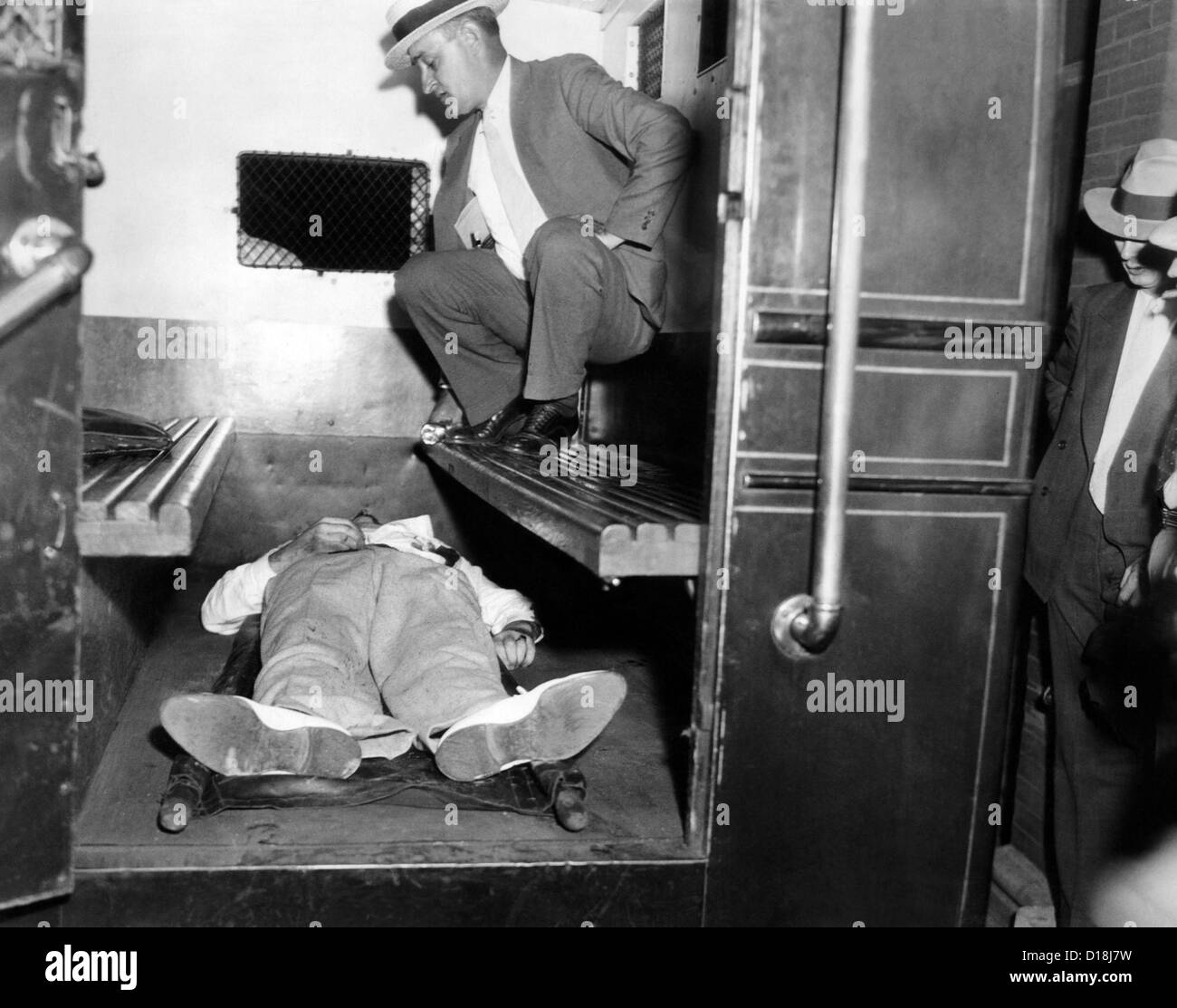 John Dillinger, dead with toes up in a police patrol wagon, is taken from the scene of his killing by FBI agents - Stock Image