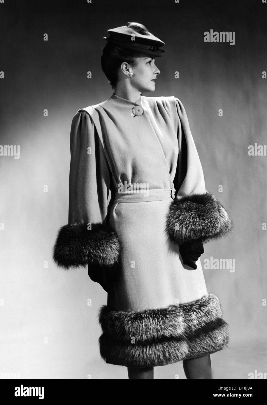 Luxurious fur trimmed dress of 1945, by Hans Geiger of New York. It features extremely broad padded shoulders, with - Stock Image