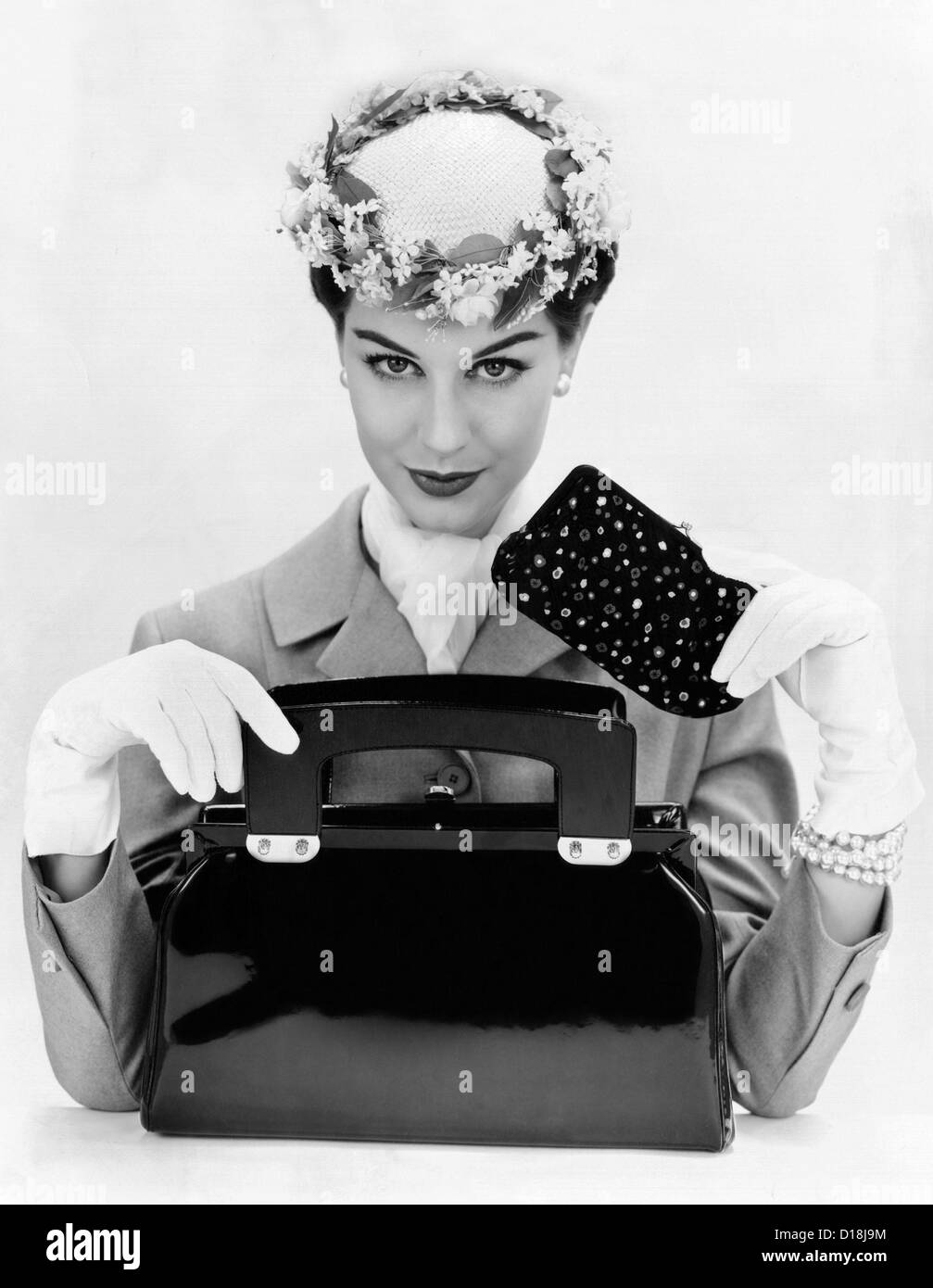 Women's accessories include a square cut, top opening, black patent leather purse. A small forward worn hat with Stock Photo