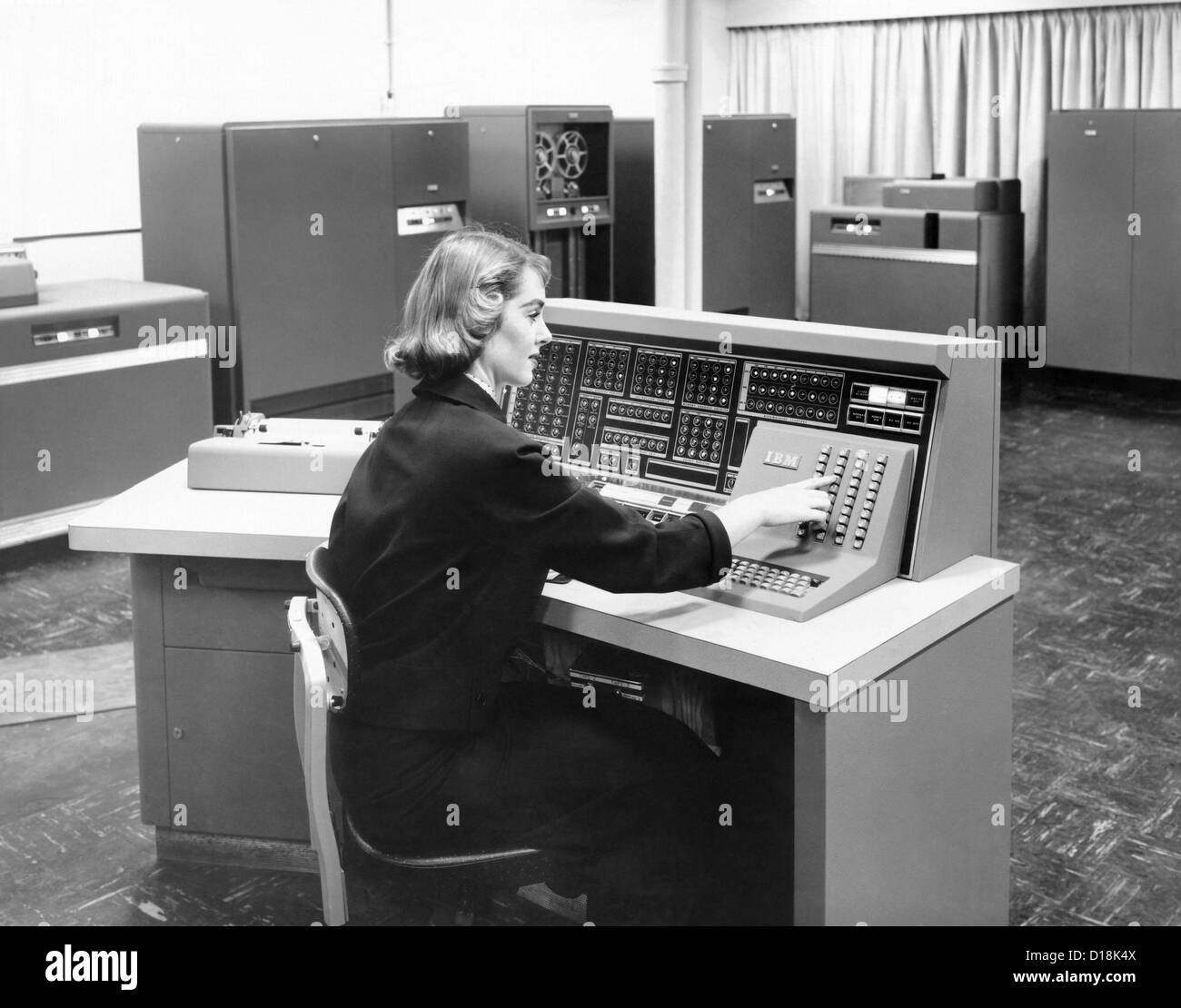 IBM 702, was a giant brain designed for business. From the operator's console, supervision was maintained over - Stock Image