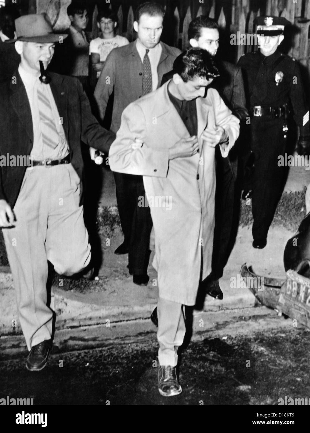 Los Angeles police take a Zoot Suiter into custody. Man wearing a super-knee length zoot suit with stuff cuffs on - Stock Image