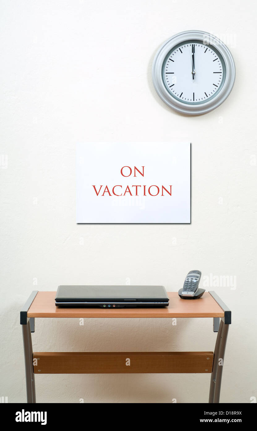 On Vacation Sign Wall With Clock Office Desk Laptop And Portable Phone